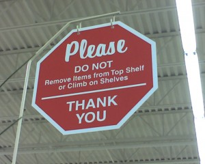 "Hobby Lobby sign: ""Please do not remove items from top shelf or climb on shelves. thank you"""
